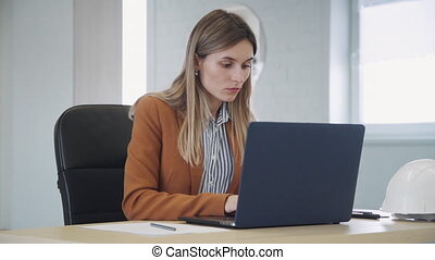Intelligent and concentrated collar worker in formal wear clothes sitting behind table in modern coworking place with bright interior office. Woman using laptop and making notes on document