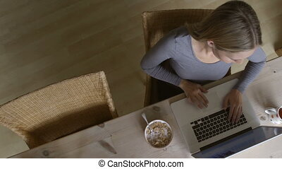 Ariel view of a young woman using her laptop at breakfast time