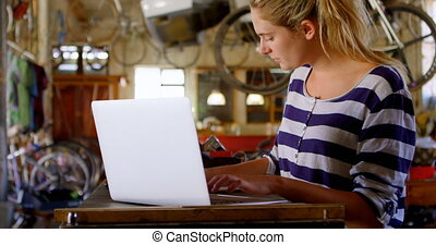 Woman using laptop at workshop 4k - Beautiful woman using...