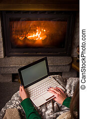 Woman using laptop by the fireplace at home