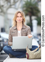 Woman using laptop computer in town