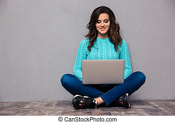 Woman using laptop computer on the floor