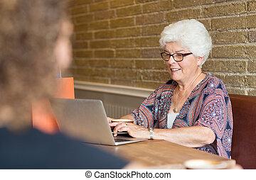 Woman Using Laptop In Coffeeshop