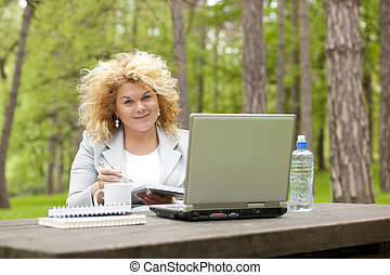 Woman using laptop in park on wooden table