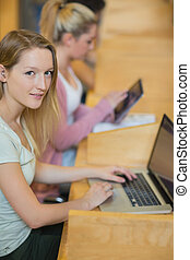 Woman using laptop looking up from studying