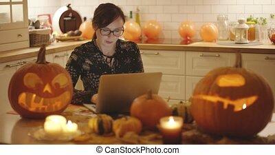 Woman using laptop near Halloween decorations
