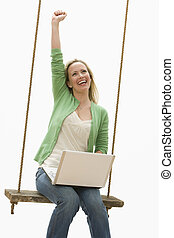 Woman Using Laptop on a Swing