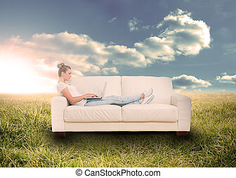 Woman using laptop on couch in field - Woman using laptop on...