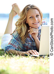 Woman using laptop outside on a sunny day