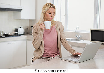Woman using laptop while drinking c