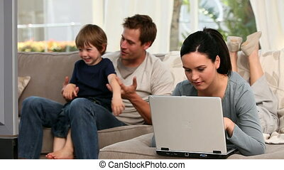 Woman using laptop while her boy and husband are watching tv...