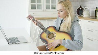 Woman using laptop while playing guitar - Young beautiful...
