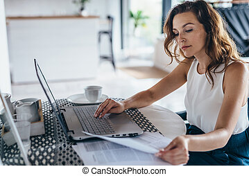 Woman using laptop while sitting at table. Young businesswoman sitting in kitchen and working on laptop.