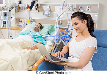 Woman Using Laptop While Sitting By Patient Resting In Bed -...