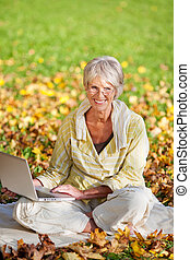 Woman Using Laptop While Sitting In Park