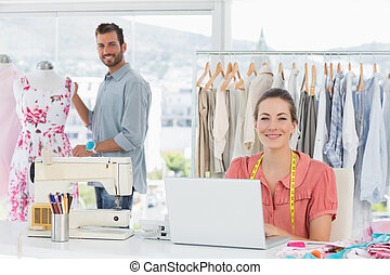 Woman using laptop with fashion designer working at studio...