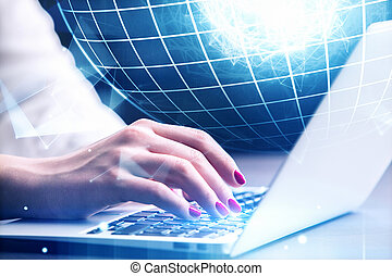 Woman using laptop with globe