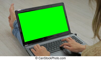Woman using laptop with green screen