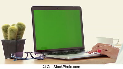 Woman using laptop with key green screen.