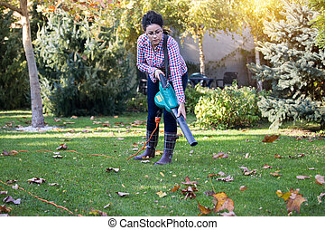 Woman using leaf blower in garden - Pretty young woman using...