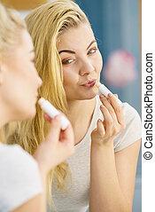 Woman using lip balm on her lips