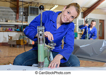 Woman using machine to punch holes in material