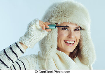 woman using mascara isolated on winter light blue background