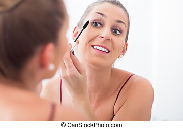 Woman using mascara on her eyelashes