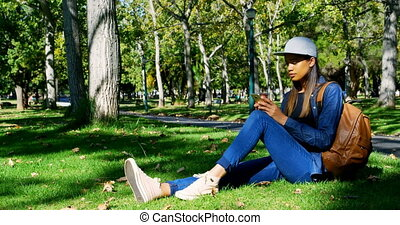 Woman using mobile in the park 4k - Beautiful woman using...
