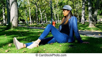 Woman using mobile in the park 4k