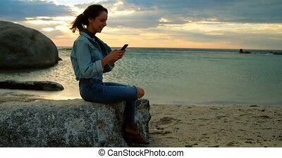 Woman using mobile phone at beach 4k - Beautiful woman using...