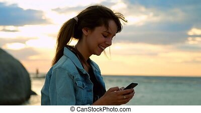 Woman using mobile phone at beach 4k - Close-up of woman...