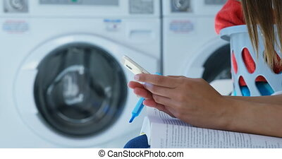 Woman using mobile phone at laundromat 4k - Mid section of...
