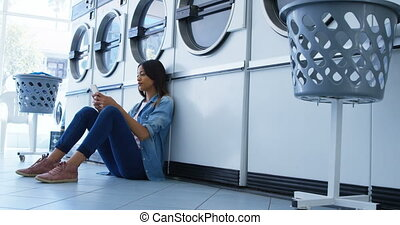 Woman using mobile phone at laundromat 4k - Smiling woman...
