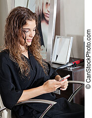 Woman Using Mobile Phone At Parlor
