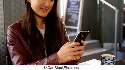 Woman using mobile phone at restaurant 4k - Beautiful woman...