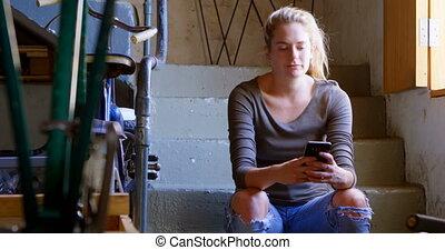 Woman using mobile phone at workshop 4k - Beautiful woman...