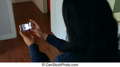 Woman using mobile phone in living room 4k - Woman using ...