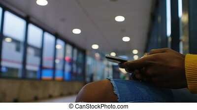 Woman using mobile phone in subway 4k - Mid section of woman...