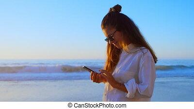 Woman using mobile phone in the beach 4k - Beautiful woman...