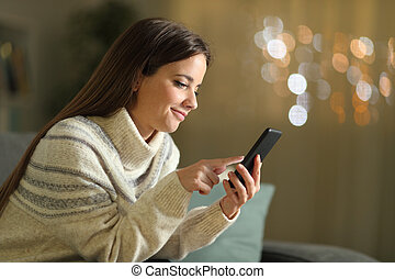 Woman using mobile phone in the night at home in winter