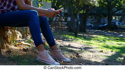 Woman using mobile phone in the park 4k