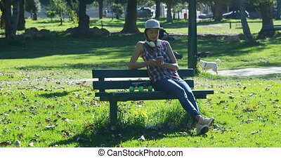 Woman using mobile phone on bench 4k - Woman using mobile...