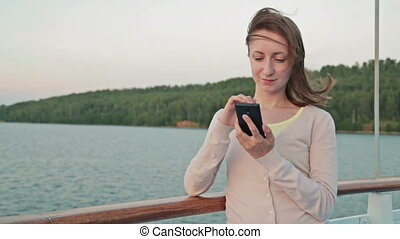 Woman using mobile phone on cruise ship - Young beautiful...