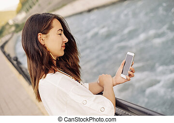 Woman using mobile phone on embankment of river