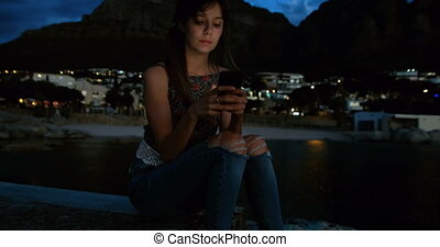 Woman using mobile phone on promenade at beach 4k - Smiling...