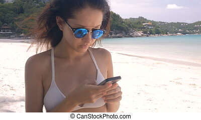 Woman using Mobile Phone on the beach