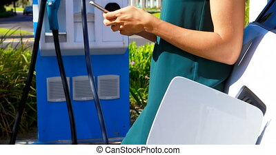 Woman using mobile phone while charging electric car 4k -...