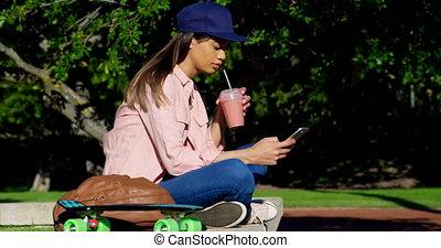 Woman using mobile phone while having juice 4k