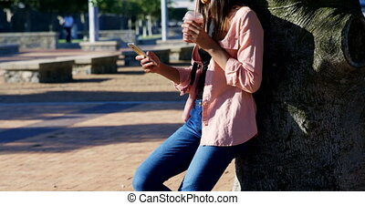 Woman using mobile phone while having juice in park 4k -...